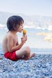 2 счастливых дет, братья мальчика, есть мороженое на пляже Стоковое Изображение