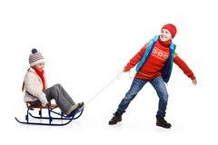 2 счастливых дет в одеждах зимы на скелетоне Стоковое Фото