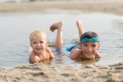 2 счастливых дет лежа в воде на пляже лета Стоковые Изображения