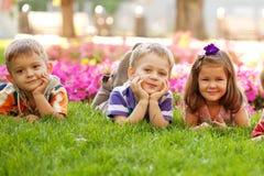 3 счастливых дет лежа на траве Стоковая Фотография RF