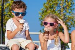 3 счастливых дет есть мороженое около бассейна на Стоковое фото RF