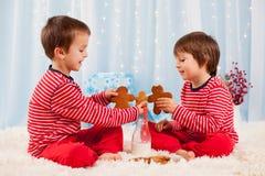 2 счастливых дет есть печенья на рождестве и питьевом молоке Стоковое Фото
