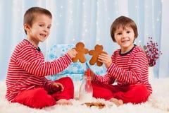 2 счастливых дет есть печенья на рождестве и питьевом молоке Стоковое Изображение RF