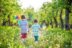 2 счастливых дет играя в саде с ветрянкой Стоковые Фотографии RF