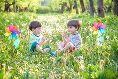 2 счастливых дет играя в саде с ветрянкой Стоковая Фотография