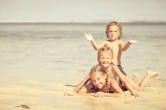 3 счастливых дет играя на пляже Стоковые Фотографии RF