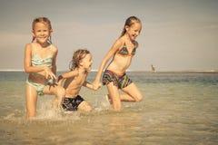3 счастливых дет играя на пляже Стоковое Изображение RF