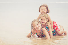3 счастливых дет играя на пляже Стоковое Фото