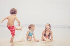 3 счастливых дет играя на пляже Стоковое Изображение