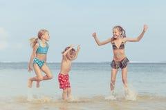 3 счастливых дет играя на пляже Стоковые Изображения RF