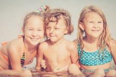 3 счастливых дет играя на пляже Стоковая Фотография RF