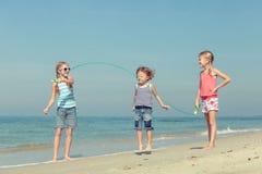 3 счастливых дет играя на пляже Стоковые Фото