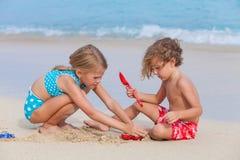 2 счастливых дет играя на пляже Стоковые Фотографии RF