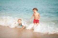 2 счастливых дет играя на пляже Стоковое Изображение