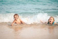 2 счастливых дет играя на пляже Стоковые Изображения