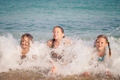 3 счастливых дет играя на пляже Стоковая Фотография