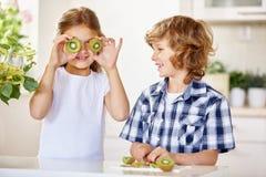 2 счастливых дет имея потеху с кивиом Стоковое Изображение