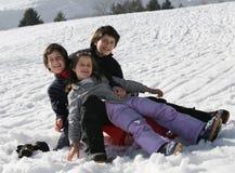 3 счастливых дет на снеге во время летних отпусков Стоковые Изображения RF