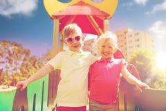 2 счастливых дет обнимая на спортивной площадке детей Стоковые Изображения