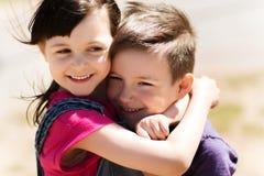 2 счастливых дет обнимая outdoors Стоковые Фотографии RF