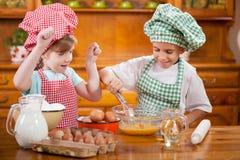2 счастливых дет подготавливая яичка для печений в кухне Стоковые Фотографии RF