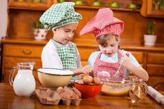 2 счастливых дет подготавливая яичка для печений в кухне Стоковые Изображения