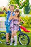 2 счастливых дет сидя на велосипеде Стоковое Изображение
