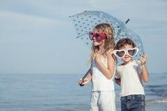 2 счастливых дет стоя на пляже на времени дня Стоковое Изображение RF