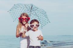 2 счастливых дет стоя на пляже на времени дня Стоковая Фотография RF