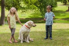 2 счастливых дет с собакой на парке Стоковая Фотография