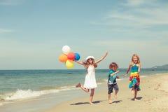 3 счастливых дет танцуя на пляже на времени дня Стоковые Изображения