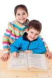 2 счастливых дет читая книгу на таблице Стоковые Изображения RF