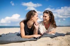 2 счастливых женских друз лежа на говорить пляжа Стоковое Изображение RF