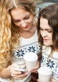 2 счастливых женских друз деля социальные средства массовой информации в умном телефоне o Стоковое фото RF
