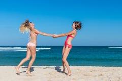 2 счастливых женских друз имея потеху и завихряясь на тропическом пляже Dua острова Бали, Nusa, Индонезия Стоковое Фото
