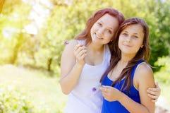 2 счастливых женских друз обнимая в зеленом лете паркуют Стоковая Фотография
