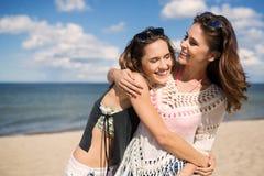 2 счастливых женских друз обнимая на пляже Стоковое фото RF
