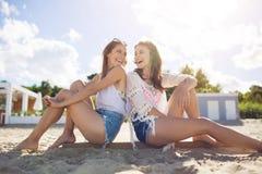 2 счастливых женских друз полагаясь друг против друга подпирают на beac Стоковые Фото