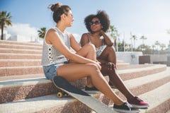 2 счастливых женских друз сидя на говорить лестниц Стоковое Фото