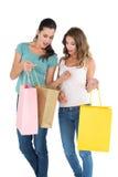 2 счастливых женских друз смотря в хозяйственные сумки Стоковая Фотография