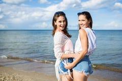 2 счастливых женских друз стоя совместно на пляже Стоковые Фотографии RF