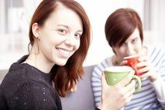 2 счастливых женских друз с кофейными чашками Стоковая Фотография RF
