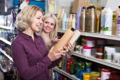 2 счастливых женщины выбирают шампунь Стоковая Фотография