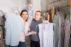 2 счастливых женщины выбирая одежды спать Стоковое фото RF