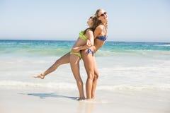 2 счастливых женщины в бикини и солнечных очках имея потеху на пляже Стоковые Изображения