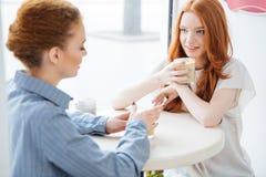 2 счастливых женщины говоря и выпивая кофе в кафе Стоковое Фото