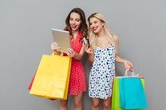 2 счастливых женщины держа хозяйственные сумки Стоковые Фото