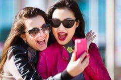 2 счастливых женщины делая фото selfie Стоковая Фотография