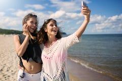 2 счастливых женщины на пляже принимая selfie чернью Стоковые Фотографии RF