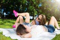 2 счастливых женщины ослабляя на парке лежа на одеяле Стоковое Изображение